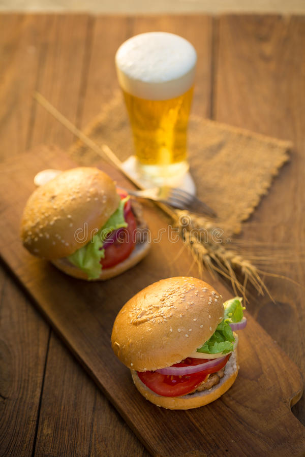 Cheese burger with grilled meat, cheese, tomato, on craft paper. On wooden surface. Fast food template stock photography