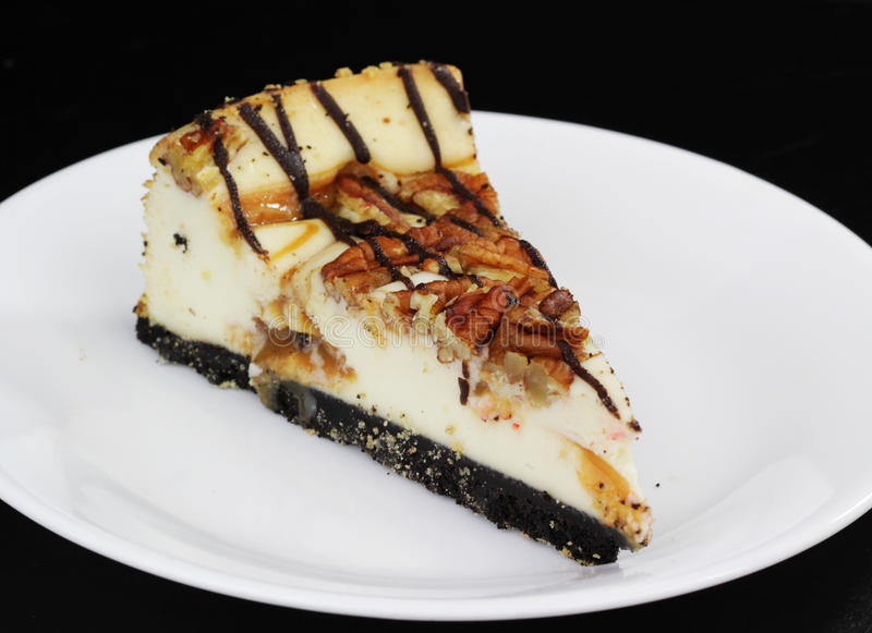 Cheese Cake. A slice of caramel filled, chocolate crusted, nut sprinkled cheese cake on a white plate stock photos