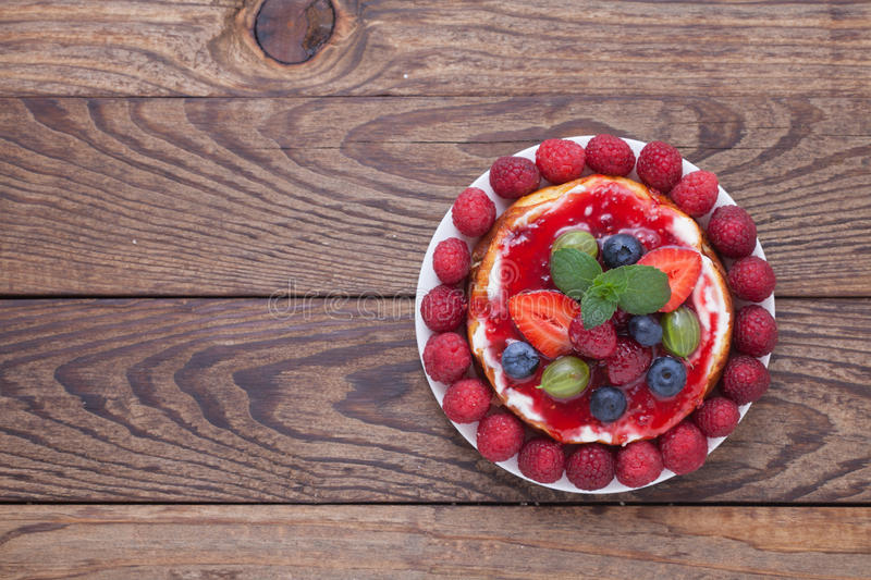 Cheese cake with berries on wooden table. stock image