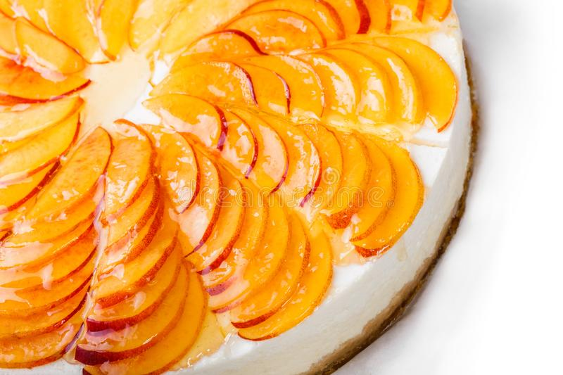 Cheese cake with peach slices isolated on white background. Bakery and pastry stock image