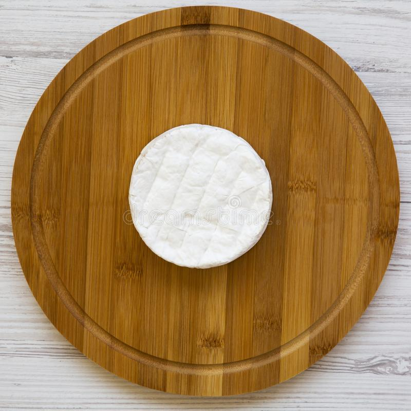 Cheese camembert on a bamboo board on a white wooden background, top view. Food for wine. From above, flat lay.  royalty free stock image