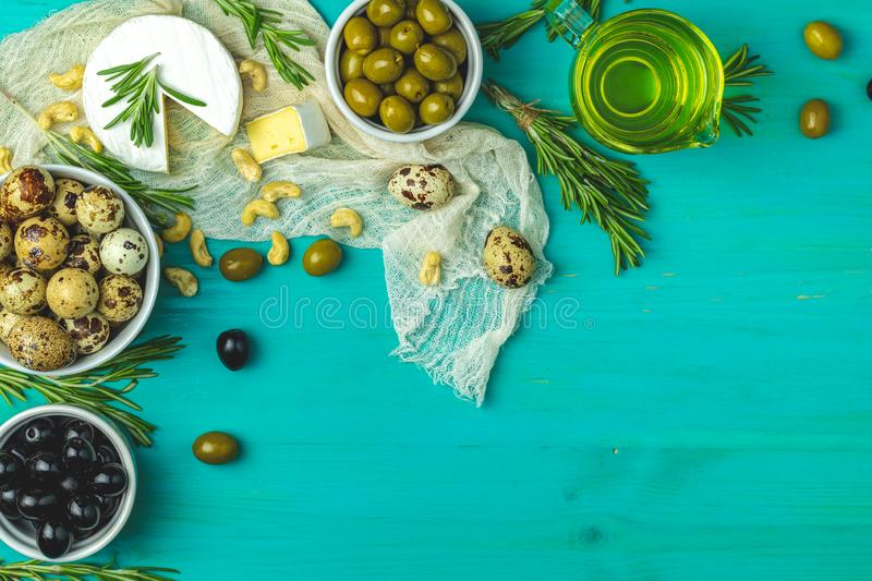 Cheese camembert, black and green olives, quail eggs, olive oil. Set of cheese camembert, black and green olives, quail eggs on plates, olive oil and rosemary royalty free stock photo