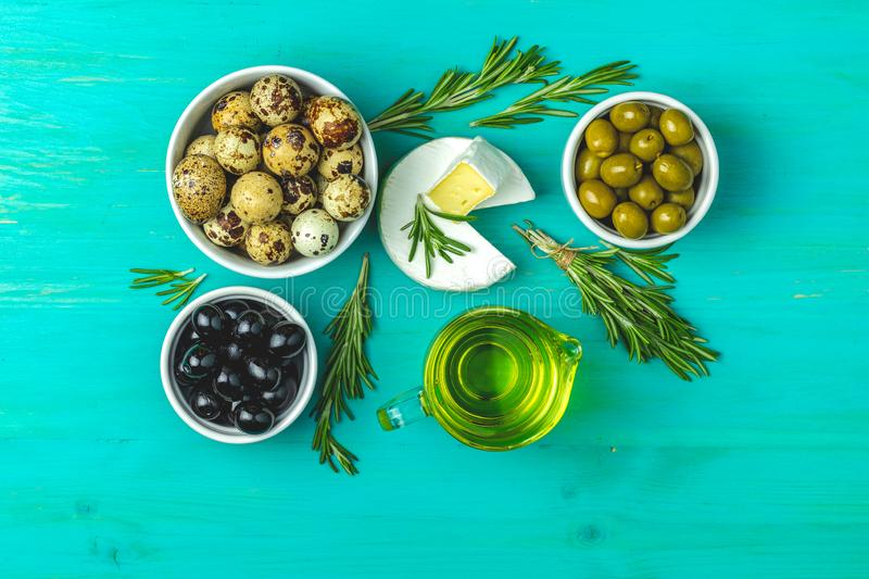 Cheese camembert, black and green olives, quail eggs, olive oil. Set of cheese camembert, black and green olives, quail eggs on plates, olive oil and rosemary royalty free stock photos