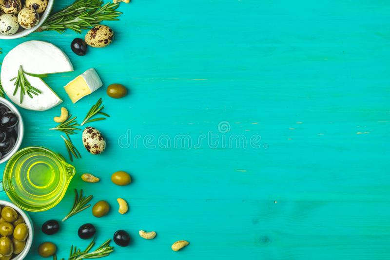 Cheese camembert, black and green olives, quail eggs, olive oil. Set of cheese camembert, black and green olives, quail eggs on plates, olive oil and rosemary stock image