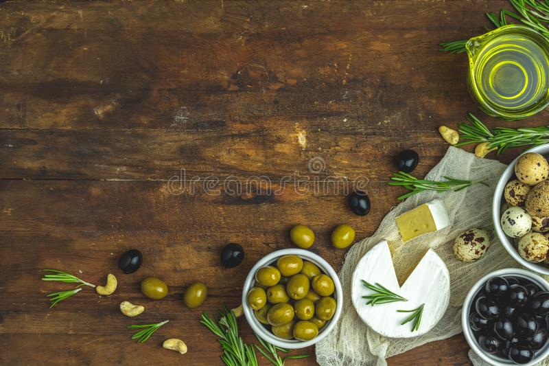Cheese camembert, black and green olives, quail eggs on plates. Set of cheese camembert, black and green olives, quail eggs on plates, olive oil and rosemary royalty free stock image