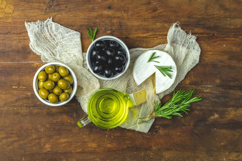 Cheese camembert, black and green olives, quail eggs on plates. Set of cheese camembert, black and green olives, quail eggs on plates, olive oil and rosemary stock image
