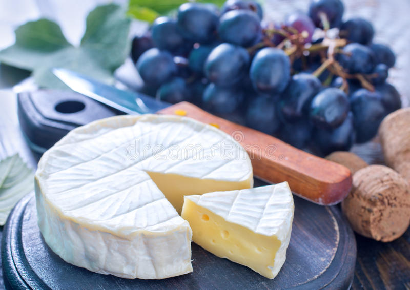 Cheese. Camembert and grape on a table stock images