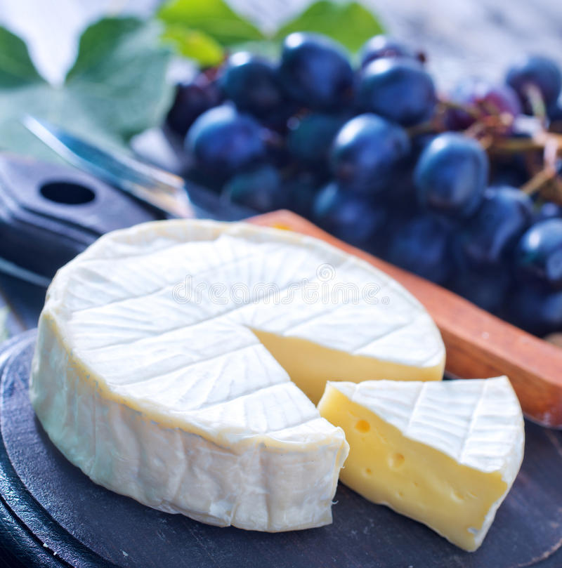 Cheese. Camembert and grape on a table royalty free stock image