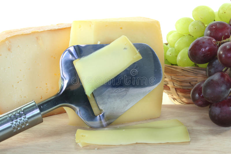 Cheese with a cheese slicer royalty free stock photography