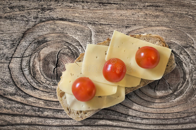 Cheese Sandwich With Three Cherry Tomatoes In Porcelain Plate Set On Old Knotted Rough Pine Wood Table royalty free stock photography
