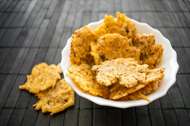 Cheese Chips Snack in a round white bowl on a black wooden background. Grain Free Dippable Crispy Cheddar Cheese Chips, Keto & Lo stock images