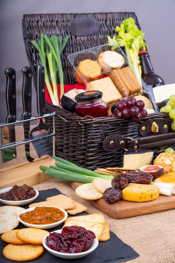Cheese and Cracker Hamper. Wicker Hamper with cheese, crackers, a selection of pickles and fruits royalty free stock photography