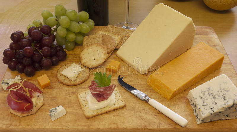 Cheese and crackers served on a wooden board stock images