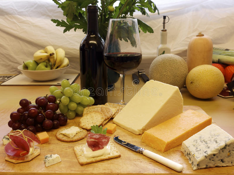 Cheese and crackers with wine and a cheese knife royalty free stock images
