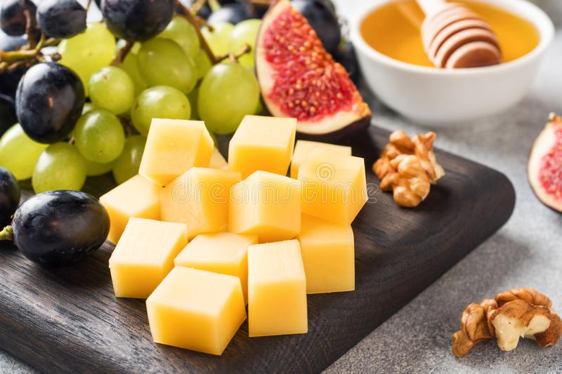 Cheese cubes, fresh fruit figs grapes Honey walnut on wooden chopping Board. Selective focus. Close up.  royalty free stock photography