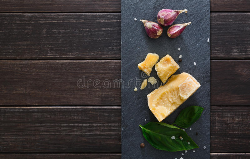 Cheese delikatessen with copy space on black stone, parmesan. Cheese delikatessen closeup on black stone desk at wooden surface background. Parmesan pieces stock images