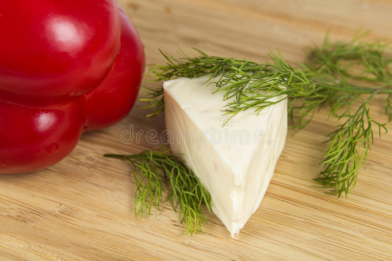 Cheese with dill and pepper. Triangle piece of cheese with dill and pepper on wooden board stock photo