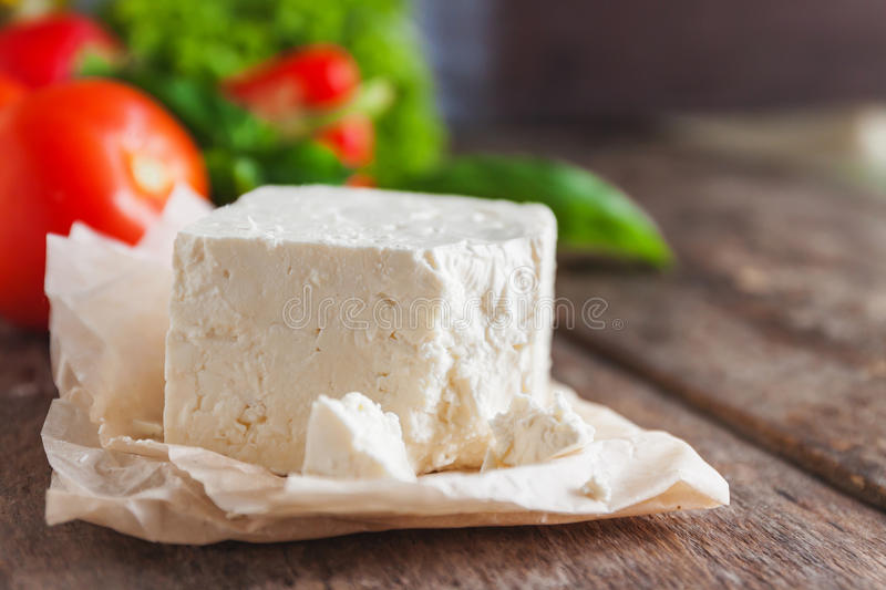 cheese feta-brynza and fresh vegetables, lettuce, tomato, cucumber, pepper on a wooden background in daylight stock images