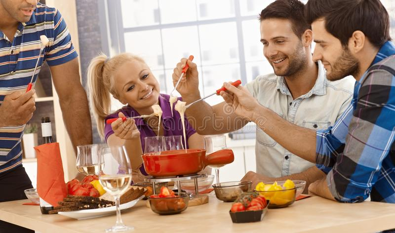 Cheese fondue with friends. Happy friends enjoying time together, having cheese fondue, smiling stock photos