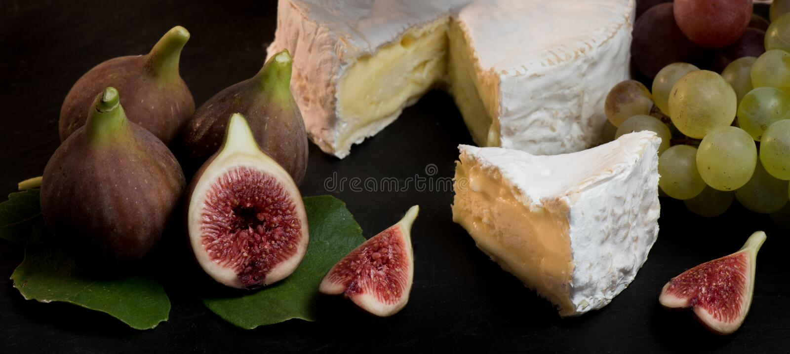 Cheese with fresh figs, camenbert on black background. Cheese with fresh figs, camenbert, France royalty free stock photo
