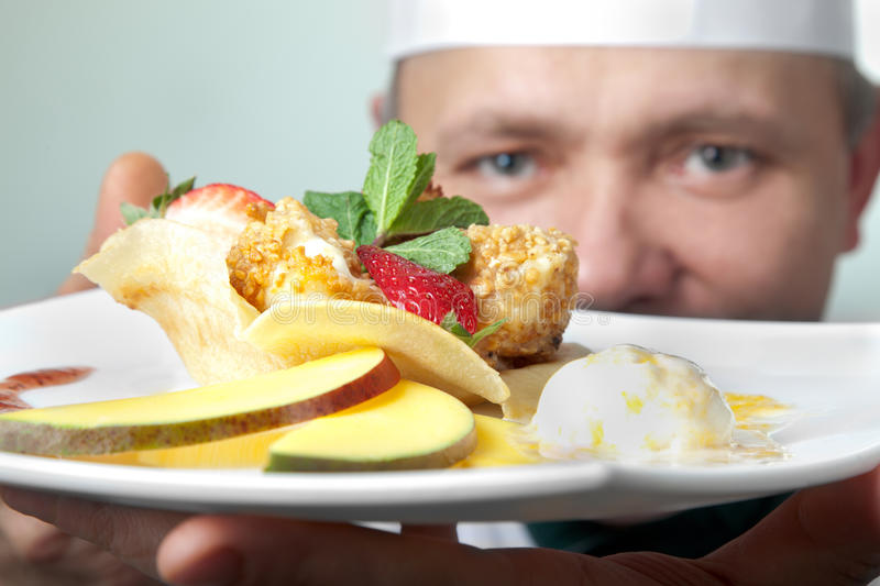 Cheese fruit dessert. Chef holding a plate with fruit dessert, focus on dish stock photography