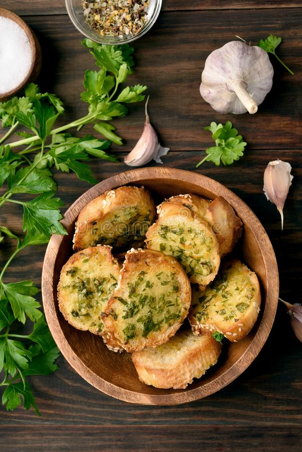 Cheese garlic toasts. In bowl over wooden background. Top view, flat lay stock photography