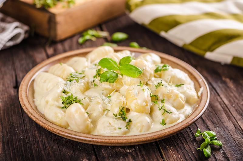 Cheese gnocchi with blue cheese sauce and galic. Herbs on top, delish food stock photos