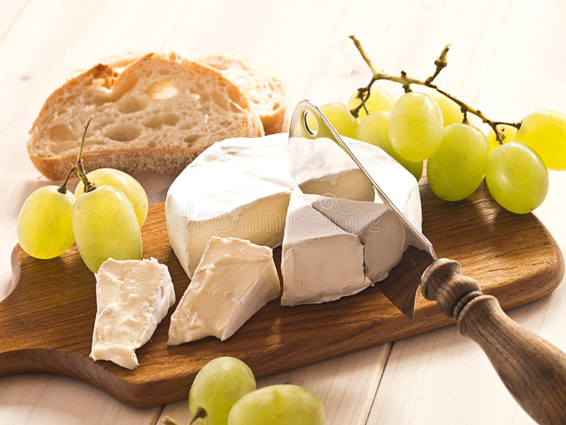 Cheese with grapes. Cheese board with Camenbert and grapes stock photos