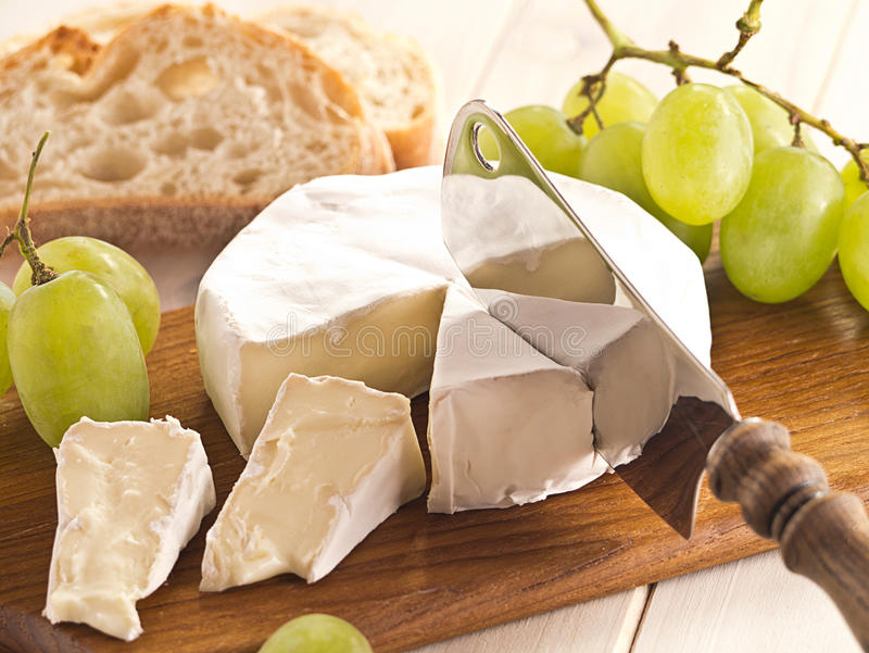 Cheese with grapes. Cheese board with Camenbert and grapes stock image
