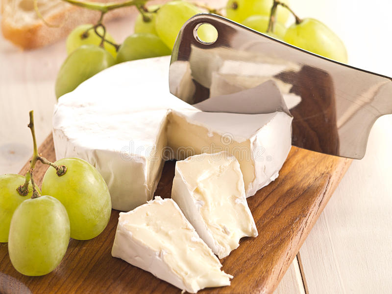 Cheese with grapes. Cheese board with Camenbert and grapes stock images