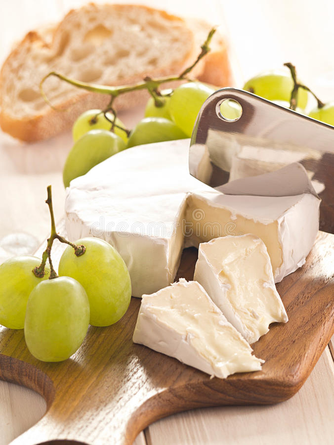 Cheese with grapes. Cheese board with Camenbert and grapes royalty free stock image
