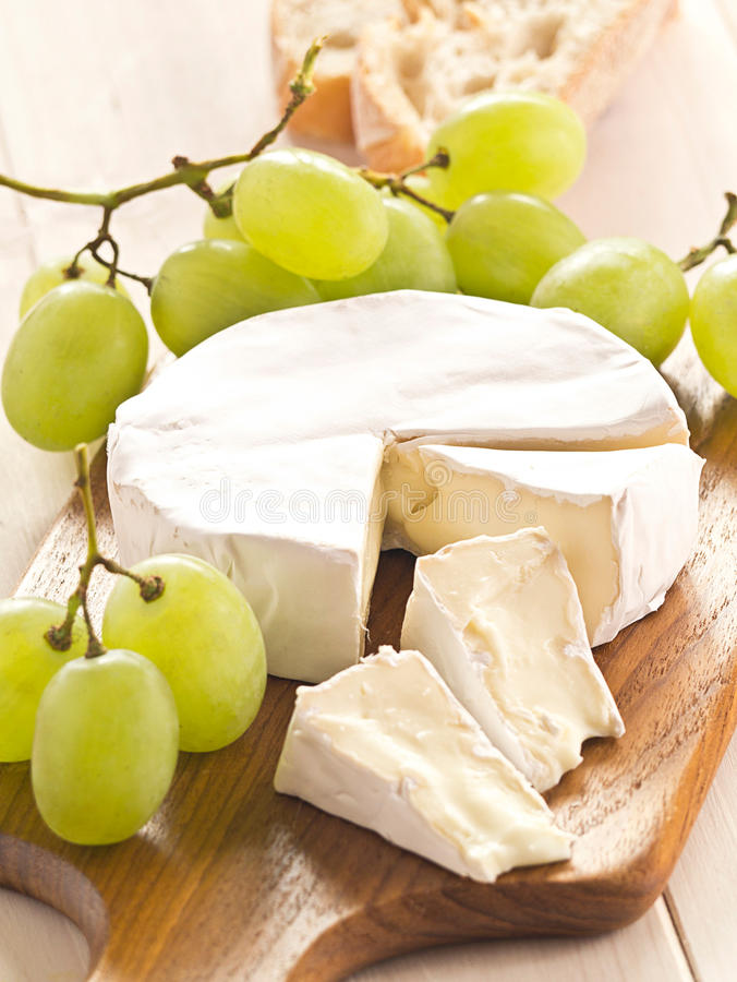 Cheese with grapes. Cheese board with Camenbert and grapes stock photo