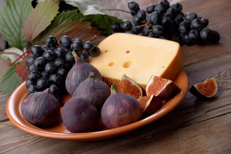 Cheese, grapes and figs on a dish royalty free stock photo