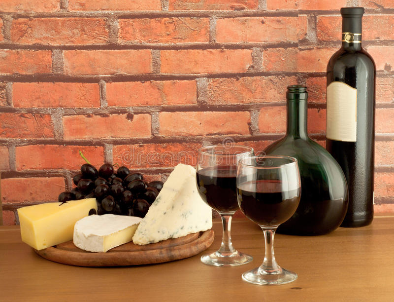 Cheese and grapes with glasses of red wine royalty free stock photos