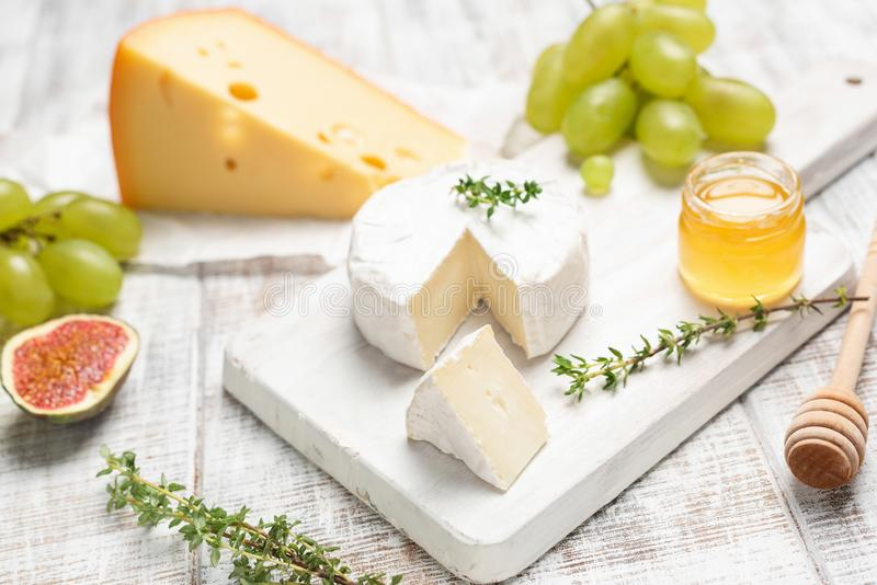 Cheese, grapes, honey and herbs on white board. Selective focus. Tasty cheese plate stock photo
