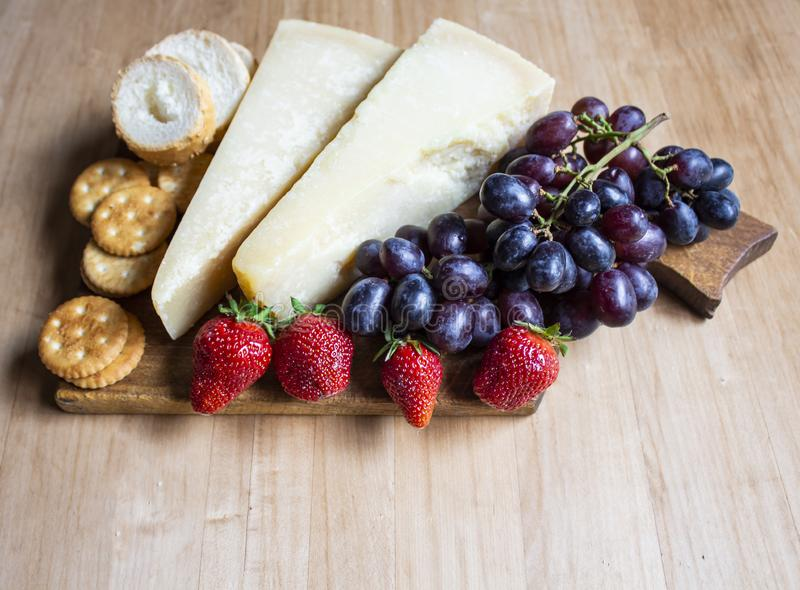 Cheese with grapes and strawberries, cracker, nuts, fruits and nuts. Cheese on a visible background. Copy space royalty free stock photo