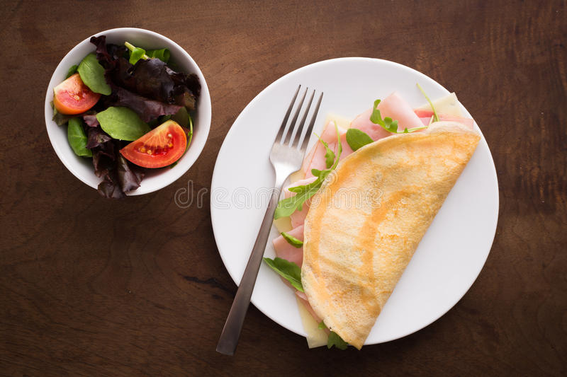 Cheese and ham crepe with salad stock photo