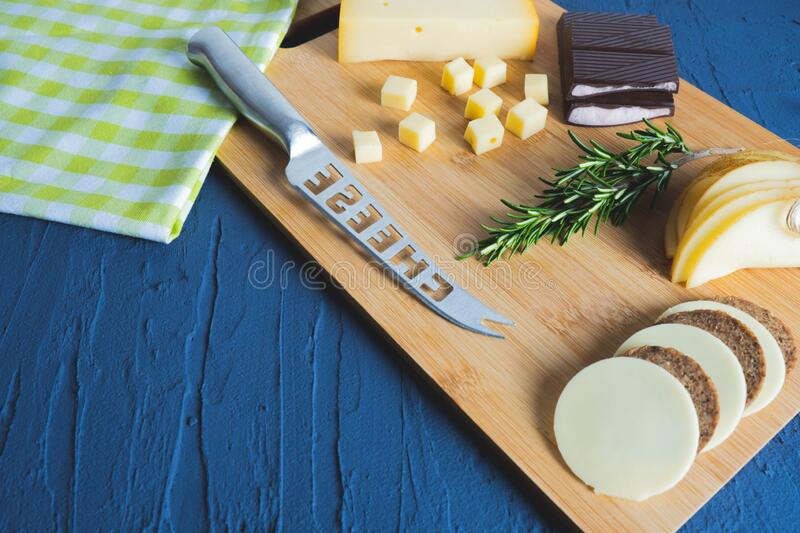 Cheese knife, chocolate, chopped cheese. On a wooden board stock image