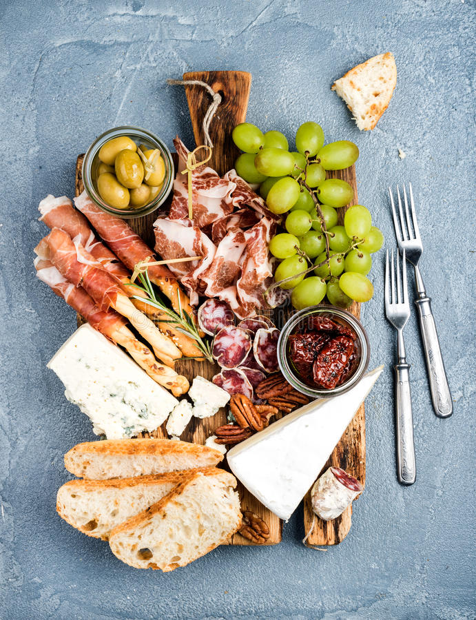 Cheese and meat appetizer selection. Prosciutto di Parma, salami, bread sticks, baguette slices, olives, sun-dried. Tomatoes, grapes and nutson rustic wooden royalty free stock image