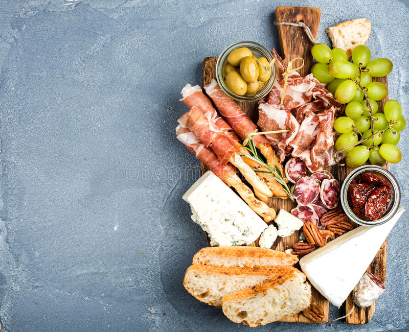 Cheese and meat appetizer selection. Prosciutto di Parma, salami, bread sticks, baguette slices, olives, sun-dried. Tomatoes, grapes and nuts on rustic wooden royalty free stock photo
