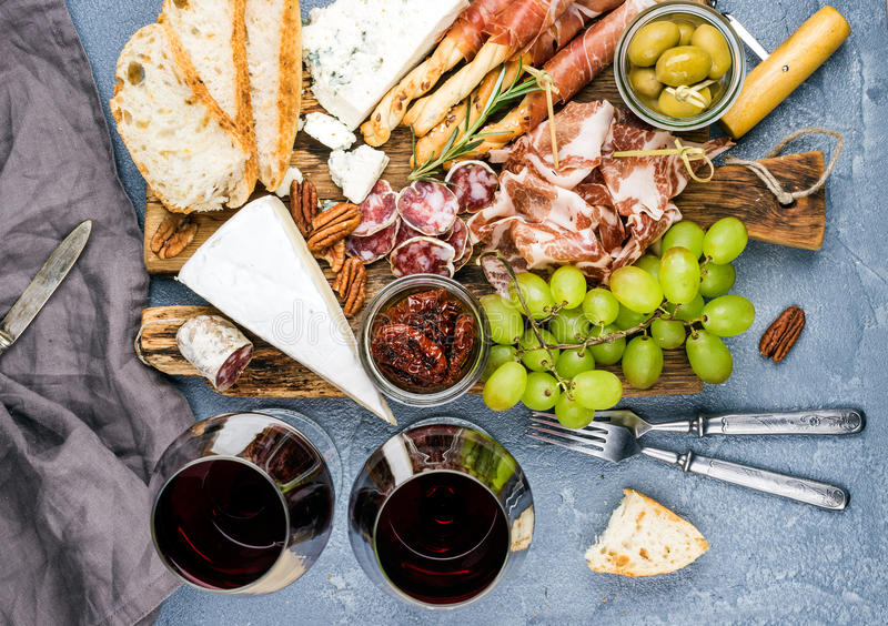 Cheese and meat appetizer selection. Prosciutto di Parma, salami, bread sticks, baguette slices, olives, sun-dried. Tomatoes, grapes and nutson rustic wooden stock images