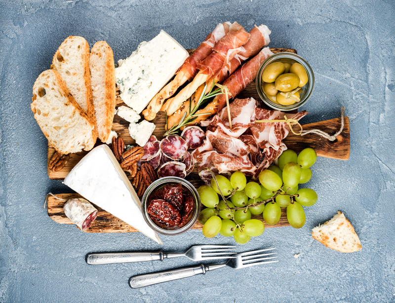 Cheese and meat appetizer selection or wine snack set. Variety of cheese, salami, prosciutto, bread sticks, baguette, honey, grap. Cheese and meat appetizer stock photography