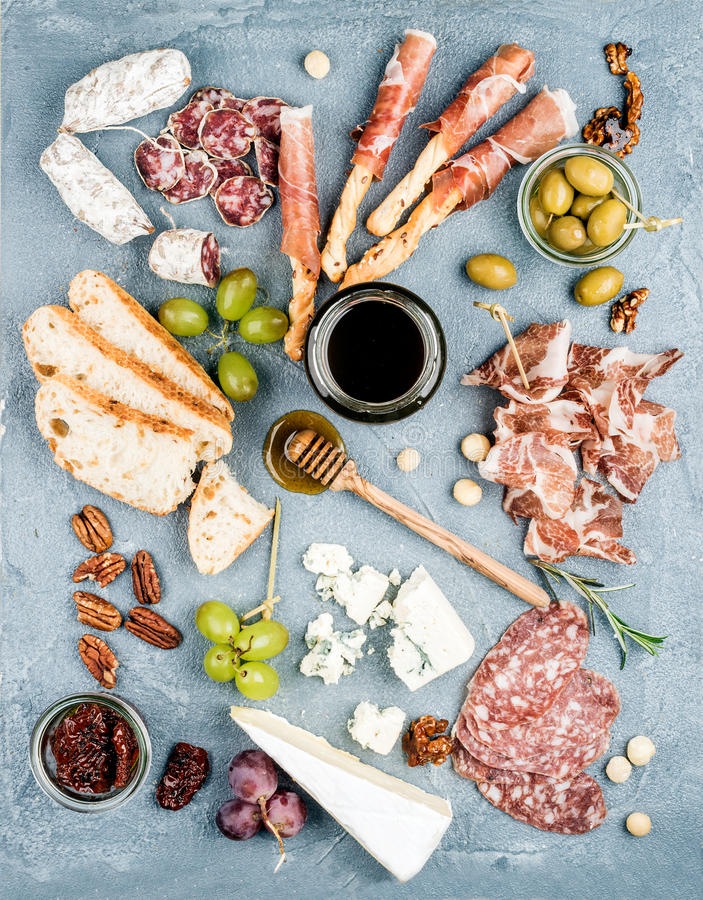 Cheese and meat appetizer selection or wine snack set. Variety of cheese, salami, prosciutto, bread sticks, baguette. Honey, grapes, olives, sun-dried tomatoes stock photos