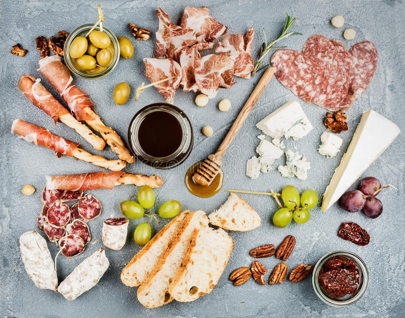 Cheese and meat appetizer selection or wine snack set. Variety of cheese, salami, prosciutto, bread sticks, baguette. Honey, grapes, olives, sun-dried tomatoes stock image
