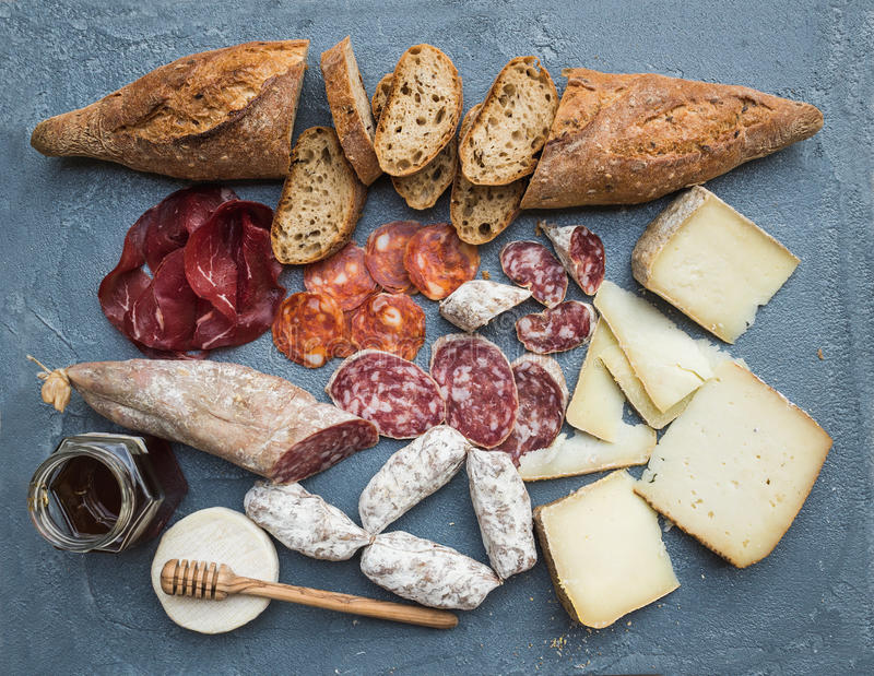 Cheese and meat appetizer selection or wine snack set. Variety of italian cheese, salami, bresaola, baguette, honey on royalty free stock image