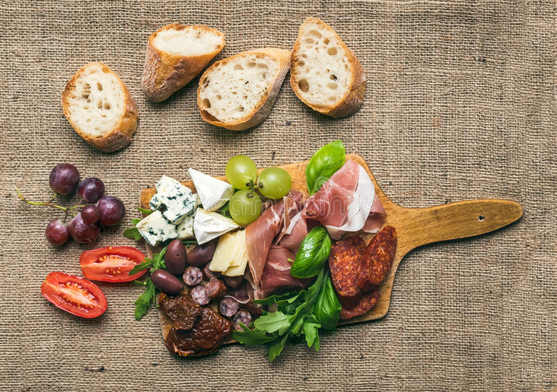 Cheese and meat platter with fresh grapes, cherry-tomatoes, olives, herbs and bread pieces on a rustic wood board over the rough. Wine set consisting of smoked stock image