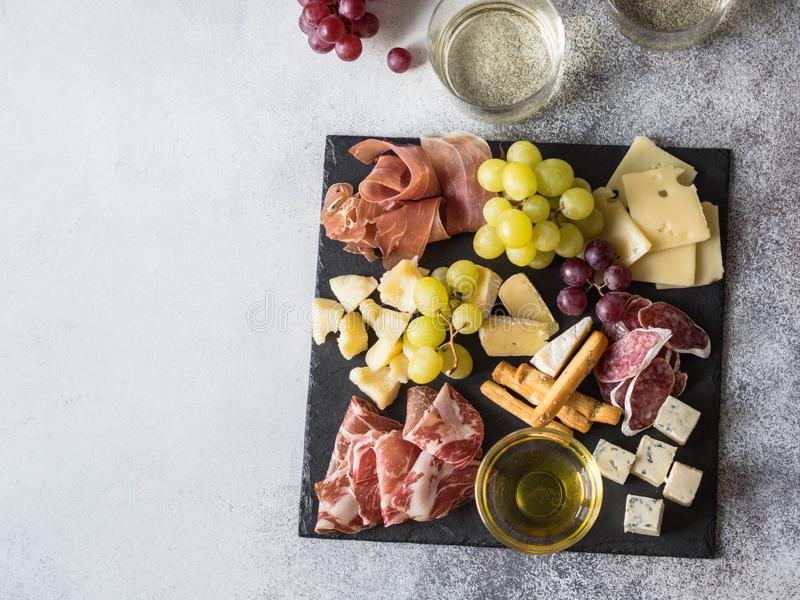 Cheese and meat wine snack set. Variety of cheese, salami, prosciutto, bread sticks, honey, grapes and two glasses with white wine royalty free stock images