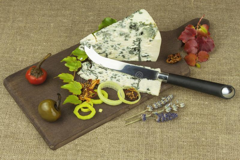 Cheese with mold on a wooden cutting board. Preparation of aromatic cheese. Stilton cheese on wooden cheese board stock images