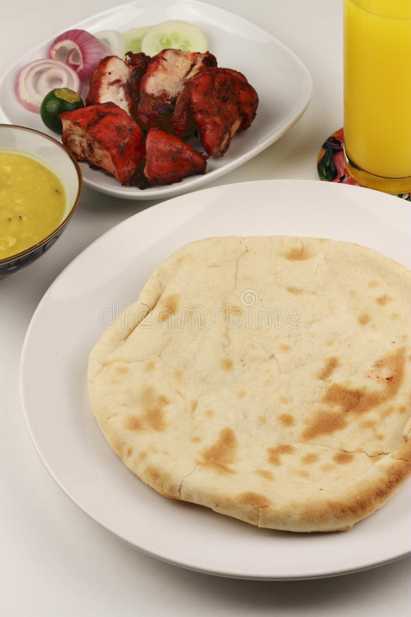 Cheese Naan. A piece of cheese naan bread with tandoori chicken, drink and gravy in the background stock photography