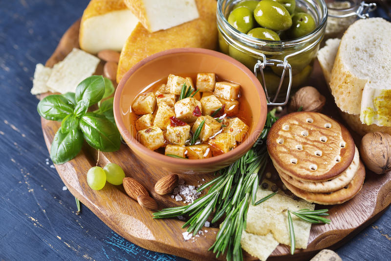 Cheese with olives and green herbs stock image